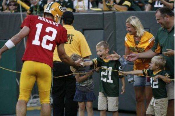 niño feliz de saludar a su jugador favorito de futbol americano