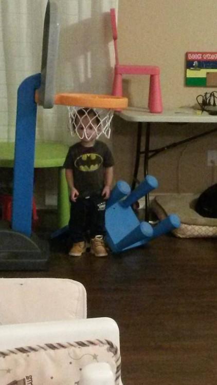 niño en una habitación de juegos dentro de una canasta de basketbol