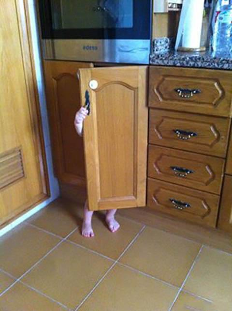 Niño escondido detrás de una puerta de un mueble de madera