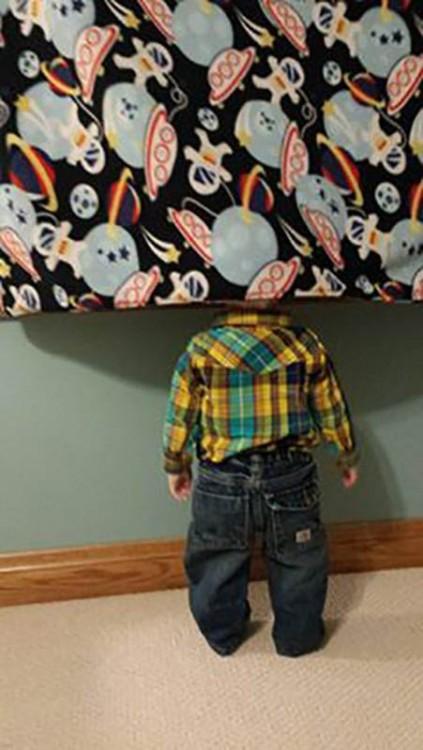 niño escondido de espaldas detrás de una cortina