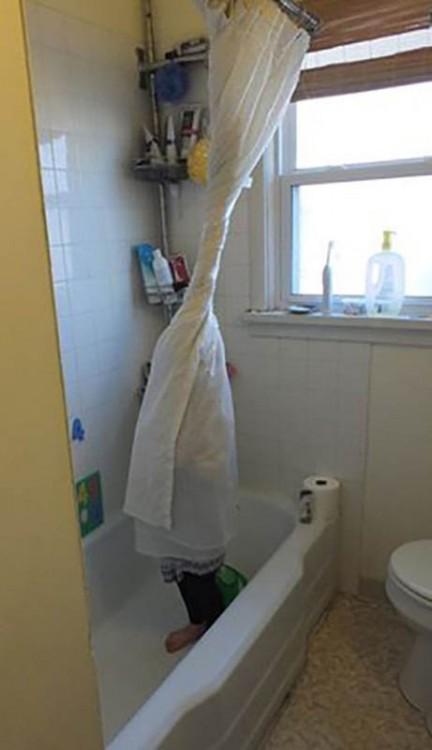Un pequeño niño enredado en la cortina de baño de una tina
