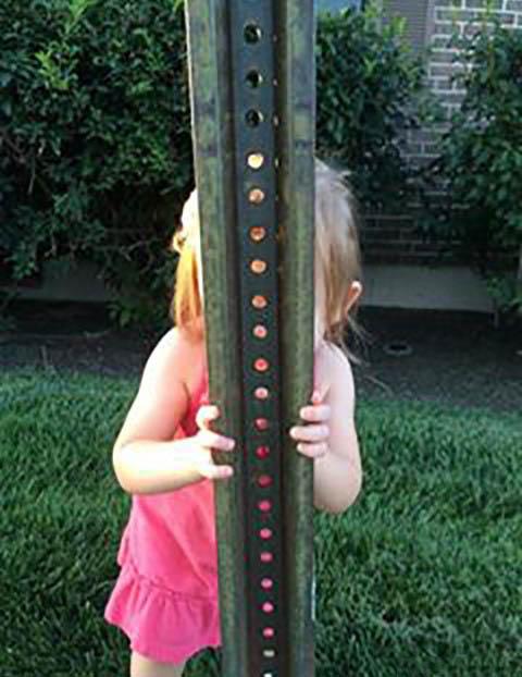 una pequeña niña detrás de un poste
