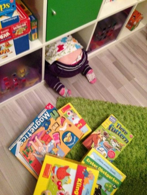 Niña dentro de un cajón de juguetes