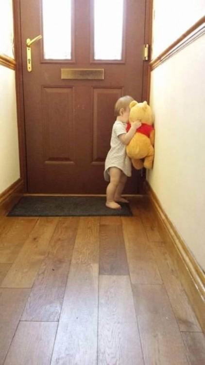 niña frente a la puerta de una casa con un peluche de winnie pooh