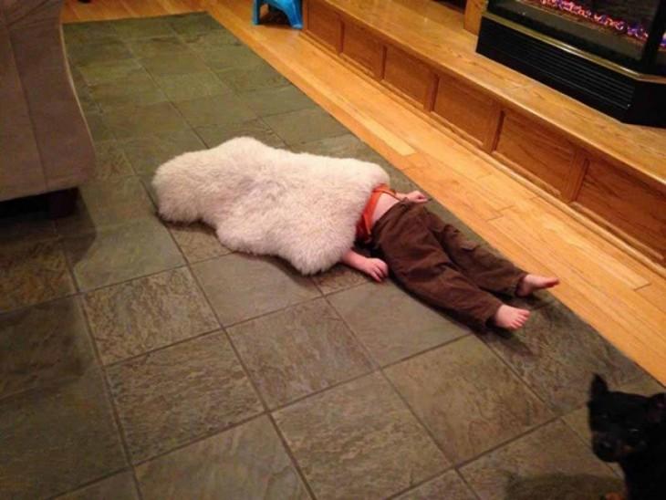 niño acostado en el suelo tapado con un tapete de peluche