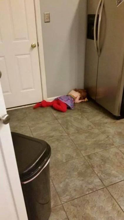 Niña acostada en el suelo frente a un refrigerador