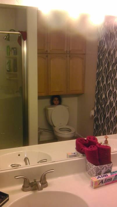 Baño de una casa donde una niña detrás del inodoro