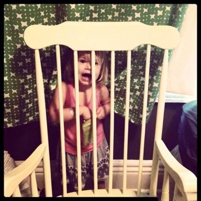 niña escondida detrás de una mecedora