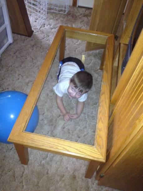 Niño escondido debajo de una mesa en la sala de una casa