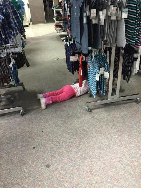 niña en el suelo entre ropa colgada en un centro comercial