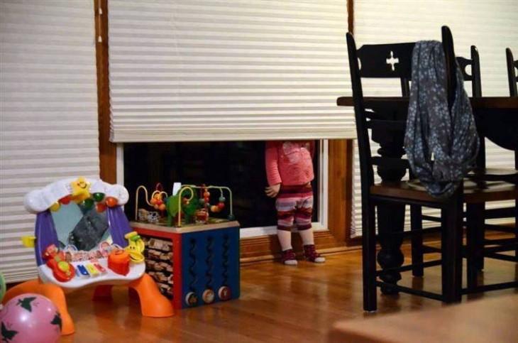 cabeza de una niña detrás de una cortina frente a un comedor