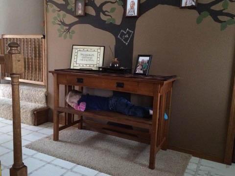una niña acostada en medio de un mueble en la sala de una casa