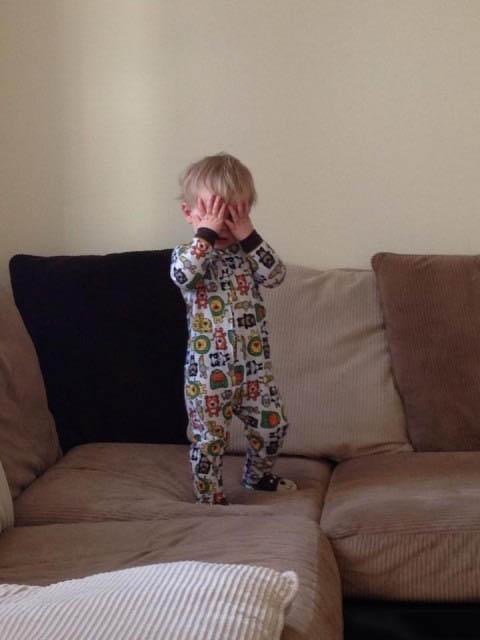 un bebé parado en un sillón tapándose los ojos