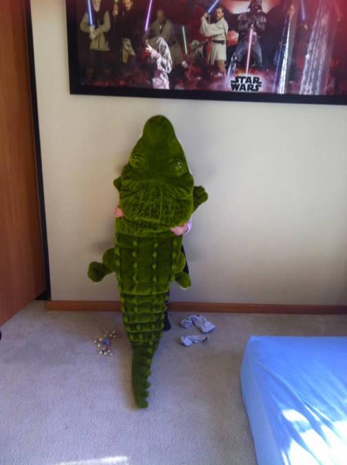 niño detrás de un cocodrilo de peluche recargado en la pared