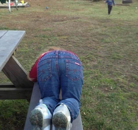una pequeña niña inclinada en una banca de un jardín