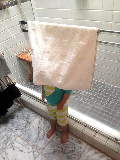 Niña parada en el baño detrás de una toalla