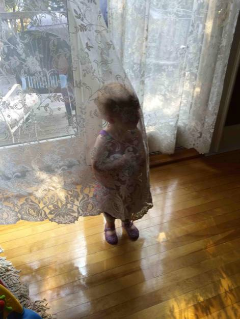 niña parada detrás de una cortina