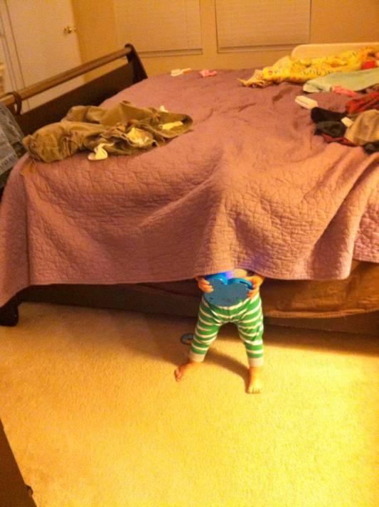 un bebé escondido debajo de la colcha de una cama