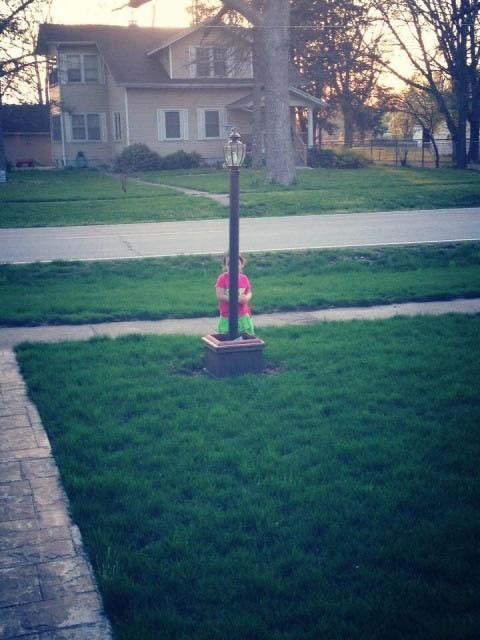 niña detrás de un poste en el jardín de una casa