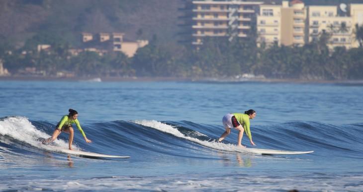 Chicas surfeando sobre la Playa Jaco en Costa Rica