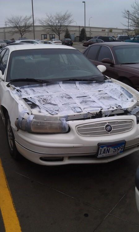 carro sin cajuela tapado con cinta adhesiva y una cobija