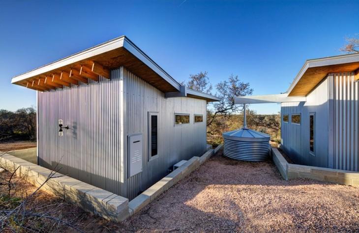 contenedor de agua entre dos cabañas construida a la orilla de un río en Texas