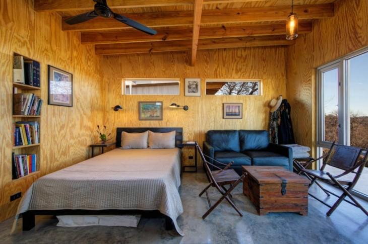 Recámara de una cabaña con una pequeña cama y una sala