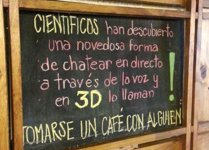 Letrero a las afueras de una cafetería que tiene una leyenda invitando a las personas a platicar