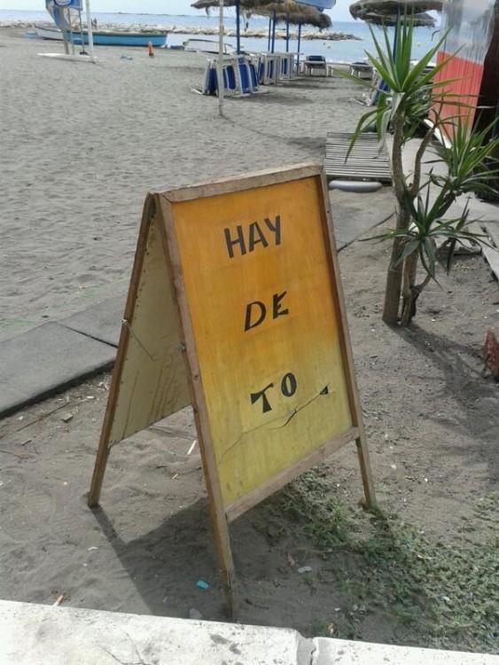 Anuncio afuera de un negocio en medio de una playa