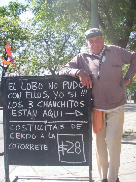 Hombre recargado en un letrero afuera de un negocio que oferta costillas de cerdo