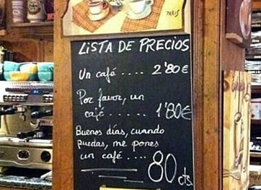 Anuncio pegado en el muro de un negocio con los precios del café