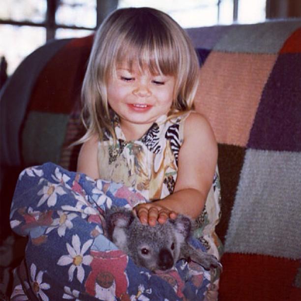 Bindi Irwin de niña acariciando a un pequeño koala