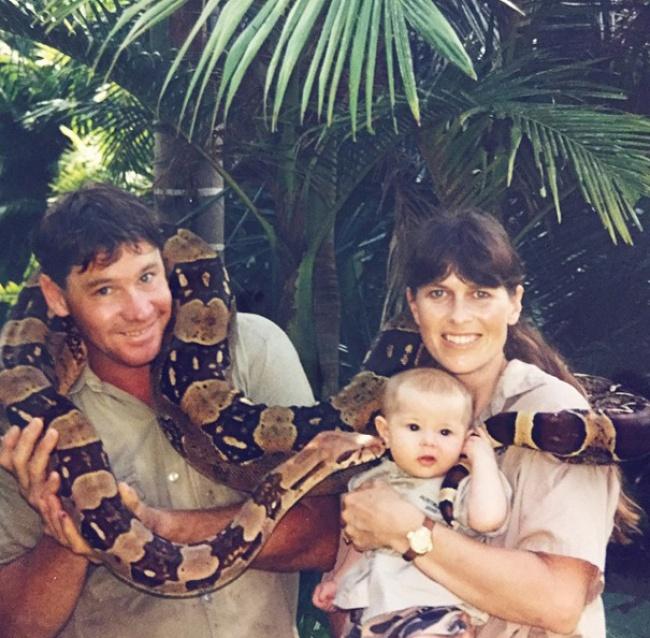 Bindi Irwin de bebé junto a su padre Steve Irwin y su madre rodeados por una serpiente
