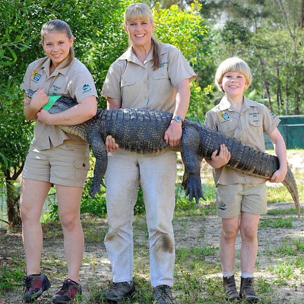Bindi Irwin junto a su hermano y su mamá sosteniendo a un cocodrilo
