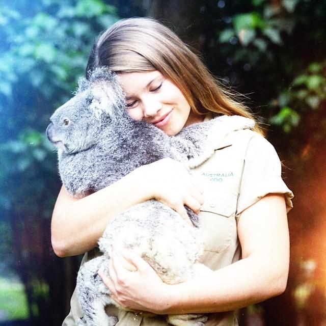 Bindi Irwin cargando y abrazando a un koala