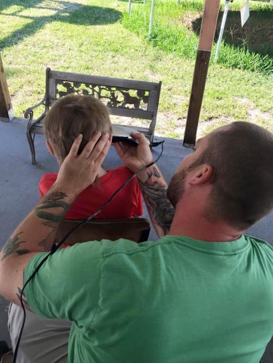 papa cortandole el cabello muy corto al niño despues de hacer las coletas