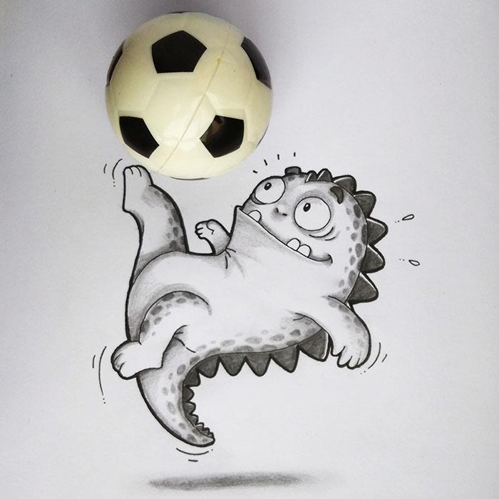 Dibujo de Drogo el dragón interactuando con una pequeña pelota de fútbol