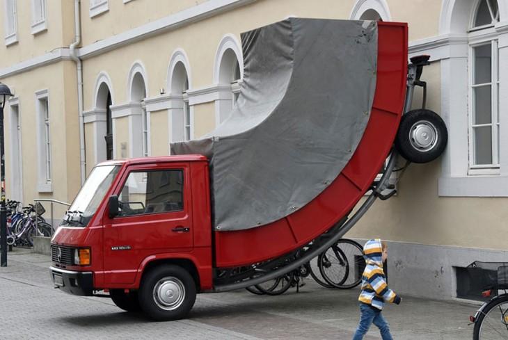 Escultura de un camión doblado hacia arriba en una pared