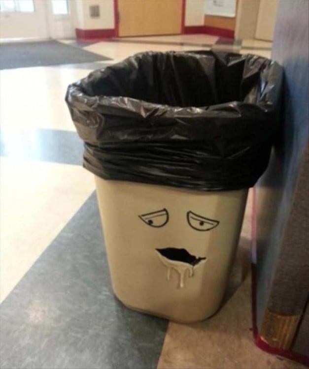 Bote de basura con una figura de cara con una bolsa negra