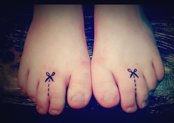 Pies de una persona con un tatuaje que simula que va a cortar los dedos