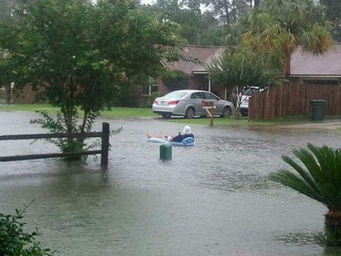 hombre recostado en un sillón que flota en el agua de una calle