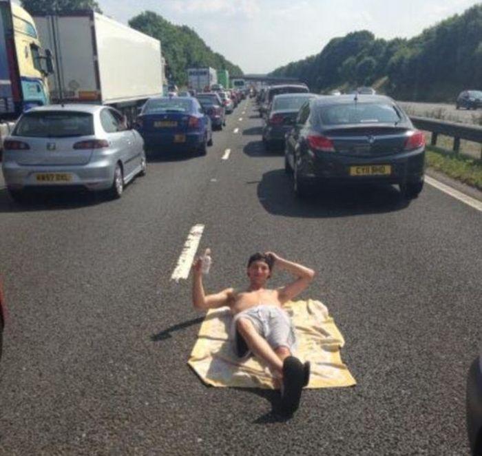 Chico acostado en el pavimento con carros detrás de él