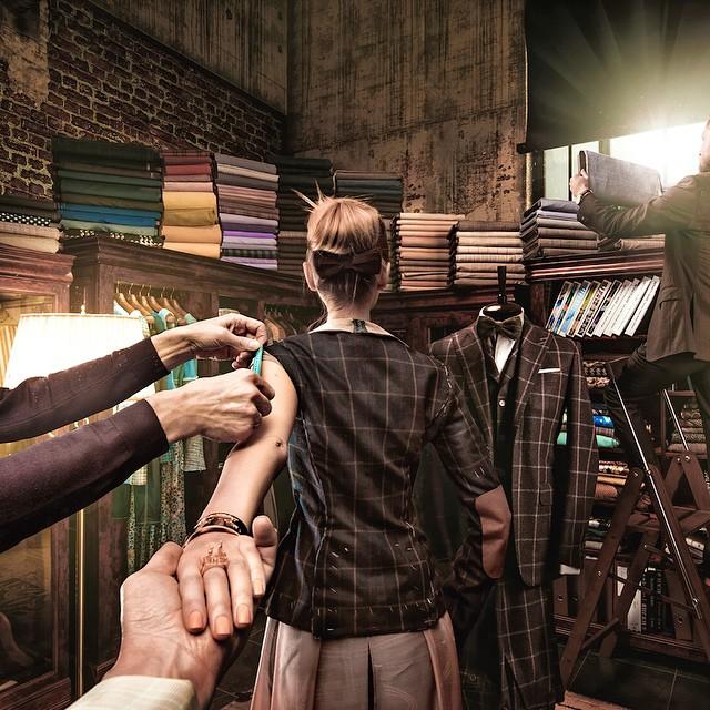 Imagen de la esposa del fotógrafo Murad Osmann donde una mano le esta tomando medidas para el vestido en un pequeño taller de costura