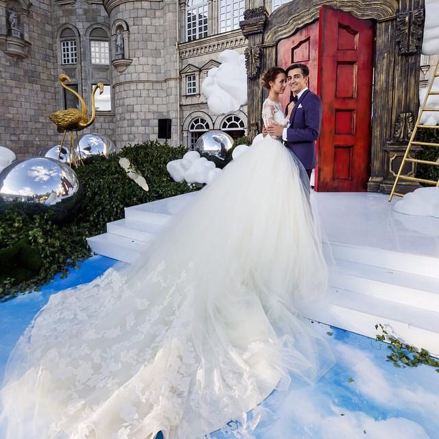 Fotógrafo Murad Osmann junto a su esposa frente a una puerta roja de un palacio