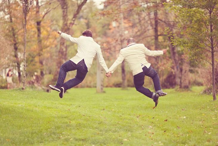 Dos chicos casados agarrados de la mano brincando juntos