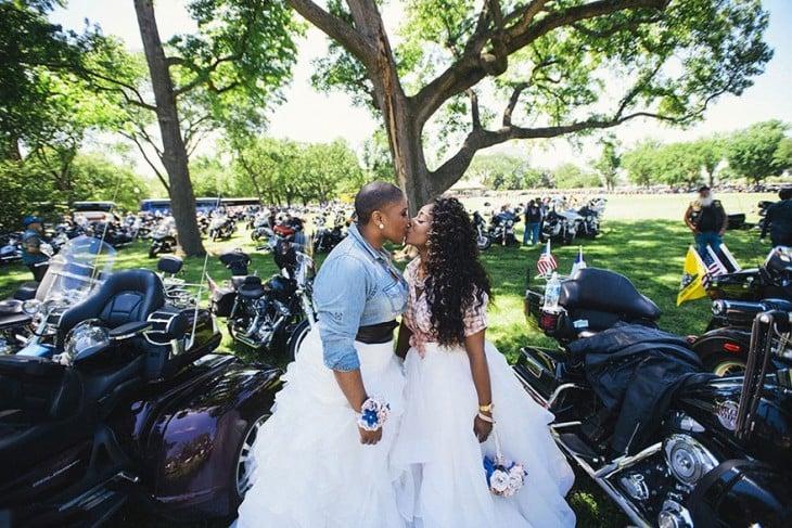 Dos chicas esposas dándose un beso y alrededor de ellas algunas motos