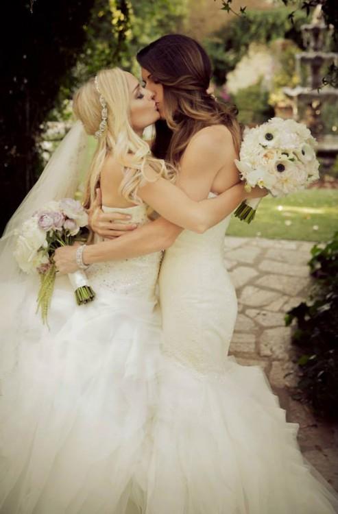 Dos mujeres recién casadas con sus vestidos de novia besándose