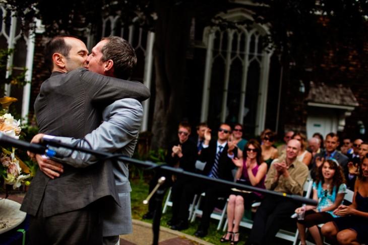 Dos hombres abrazados besándose en la boca con gente detrás de ellos