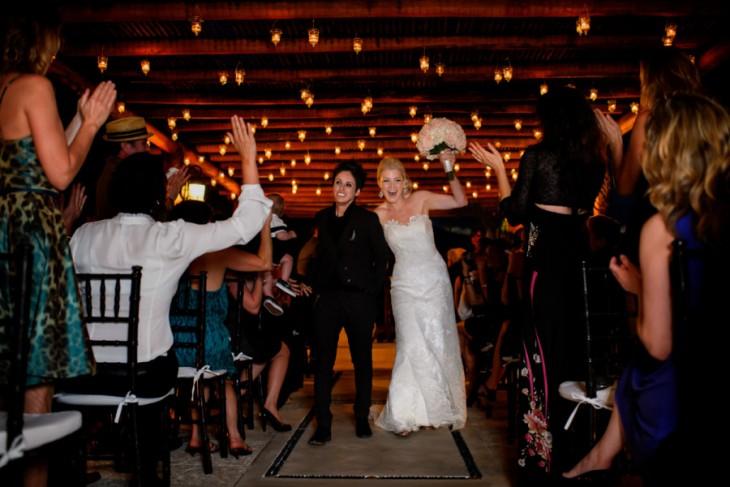 Jen and Lani recién casadas caminando por el pasillo entre sus invitados