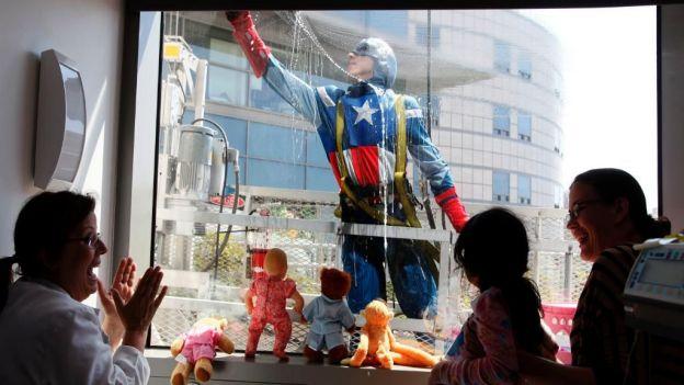 niños en el hospital asomandose por la ventana para ver a sus super heroes